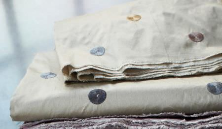 James Hare -  Regal Silk Vol 3 Fabric Collection - Pale mauve fabric placed beneath foldedpale grey fabric featuring asmall grey, brown and gold circle pattern