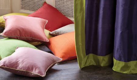James Hare -  Regal Silk Vol 3 Fabric Collection - Plain purple curtains edged in green, with plain pink, green, yellow, red, white and orange scatter cushions