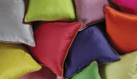 James Hare -  Regal Silk Vol 3 Fabric Collection - A pile of plain scatter cushions in bright red, purple, orange, green, yellow, grey and pink colours