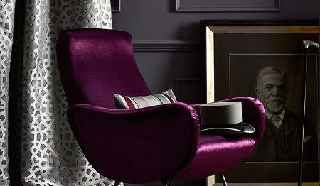 James Hare -  Richmond Velvet Fabric Collection - Silver and dark grey patterned curtains with a curved, sleek dark purple armchair with a top hat and a striped cushion