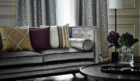 James Hare -  Richmond Velvet Fabric Collection - A round black table with a glass vase, a silver sofa,grey patterned curtains, and patterned, plain and striped cushions