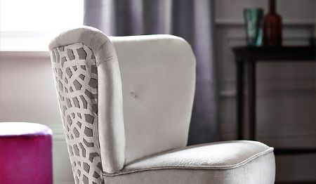 James Hare -  Richmond Velvet Fabric Collection - A small white padded chair with a grey and white patterned back, with blue-grey curtains and a round hot pink footstool