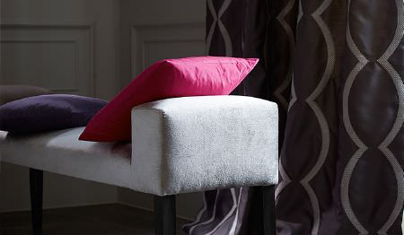 James Hare -  Richmond Velvet Fabric Collection - A white padded bench style seat with plain bright pink and purple cushions, and dark curtains with grey scalloped lines