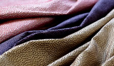 James Hare -  Shagreen Silk Fabric Collection - Swathes of slightly speckled pink and white, purple, and brown and cream coloured fabrics