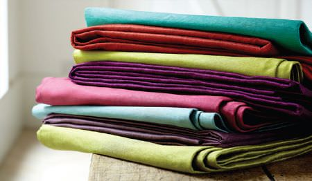 James Hare -  Soho Silk Fabric Collection - Lime green, plum, sky blue, candy pink, burgundy and aquamarine coloured plain fabrics folded and stacked in a pile
