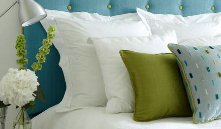 James Hare -  Soho Silk Fabric Collection - White pillows and bedding on a bed with a blue headboard, a lime green cushion, a textured grey and blue cushion and a lamp