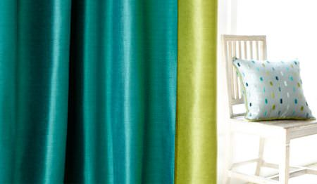 James Hare -  Soho Silk Fabric Collection - Plain curtains made in bright, slightly shiny aquamarine and lime green colours, with a white chair and a patterned cushion