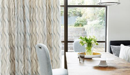James Hare -  Tempo Fabric Collection - Light beige curtain decorated with grey wavy pattern and a set of dining chairs featuring dotted pattern