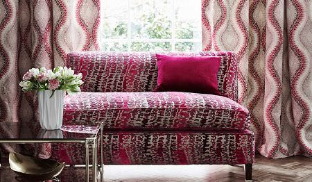 James Hare -  Tempo Fabric Collection - Beige curtains with dark red pattern and an upholstered sofa with an interesting pattern in different shades of pink