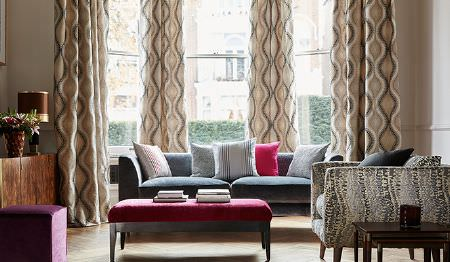 James Hare -  Tempo Fabric Collection - Modern velvet purple ottoman, dark grey sofa, and upholstered red coffee table and beige curtains with wavy red pattern