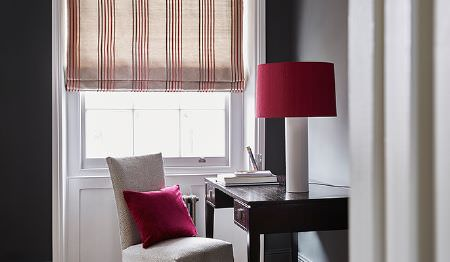 James Hare -  Tempo Fabric Collection - Transparent beige roman blinds decorated with a modern pattern of thin stripes in red and matching red cushion and lamp