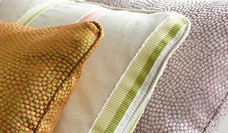 James Hare -  Tesserae Silk Fabric Collection - Lime and orange, and pink and white speckled fabrics covering two cushions, with a striped cushion in green, pink and white