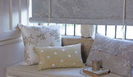 James Hare -  Westbury Silks Fabric Collection - A blind with a grey and white floral pattern, a white window seat, and grey, white and cream dotted and patterned cushions