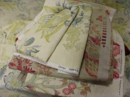Jim Dickens -  Acquitaine Fabric Collection - A stack of swatches of ornately patterned cream and beige coloured fabrics, with large green, blue, grey, gold and dark red florals