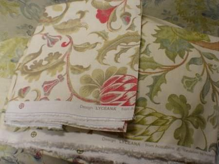 Jim Dickens -  Acquitaine Fabric Collection - Stacks  of fabrics where the raw edges are visible, all in cream, with intricate, leafy floral patterns in green, red, brown and blue shades