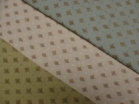 Jim Dickens -  Alicante Fabric Collection - Tiny, individual green and brown floral shapes arranged in rows with white dots on green, light brown and blue fabric backgrounds