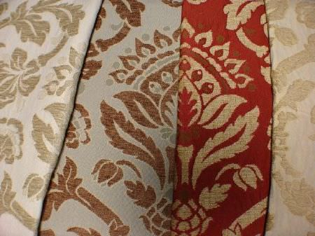 Jim Dickens -  Alicante Fabric Collection - Swatches of fabrics with the same large, ornate pattern in gold, brown and green-grey on backgrounds of cream, bright red and light blue