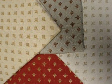 Jim Dickens -  Alicante Fabric Collection - Folds of four fabrics patterned with tiny, individual floral shapes, in cream, grey, white, red, gold, brown and green-grey