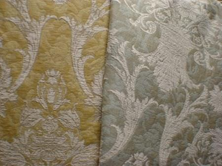 Jim Dickens -  Avalon Fabric Collection - A large, ornate, light grey pattern on blue and grey patterned fabric, as well as fabric patterned in two different shades of gold