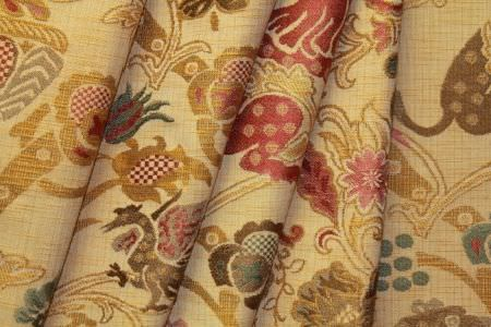 Jim Dickens -  Behram Fabric Collection - Folds of busily patterned caramel coloured fabric with red, dark brown, gold and blue designs