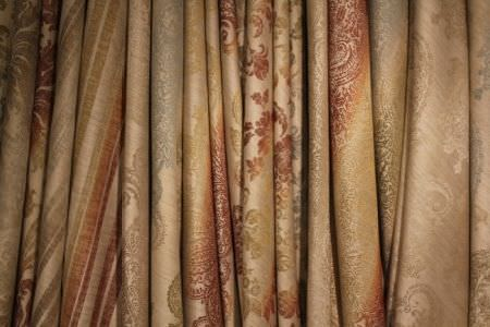 Jim Dickens -  Bohemia Linen Fabric Collection - Numerous folds of multicoloured, subtly patterned fabrics in colours such as beige, orange, light blue, gold and green
