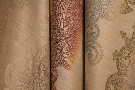 Jim Dickens -  Bohemia Linen Fabric Collection - Slightly shiny cream coloured fabrics with very detailed patterns which fade between brown, red and orange, and blue and green