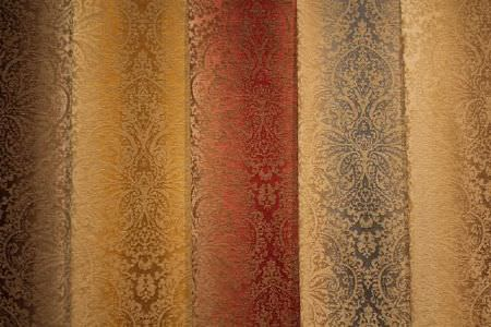 Jim Dickens -  Cambridge Fabric Collection - Swatches of fabrics with very intricate, detailed patterns in brown, yellow, red, blue and gold, all on cream backgrounds