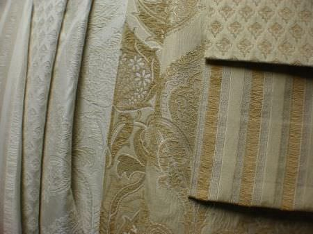 Jim Dickens -  Corsini Avalon Fabric Collection - Folds of a variety of different silver-grey coloured patterned fabrics, with some matching swatches of gold-beige coloured fabrics