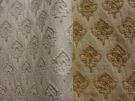 Jim Dickens -  Corsini Avalon Fabric Collection - A fold of grey fabric patterned with rows of silver crests, beside a swatch of crest patterned fabric in gold and gold-beige