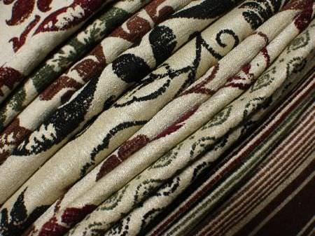 Jim Dickens -  Farnese Fabric Collection - Folds of numerous warm cream coloured fabrics, all patterned or striped in either dark red, green, brown or black