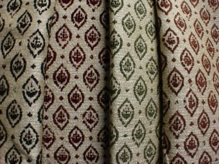 Jim Dickens -  Farnese Fabric Collection - Small blue, red, green and brown patterned ovals printed in rows over four fabrics in a beige colour