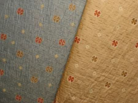 Jim Dickens -  Firenze Fabric Collection - Tiny red and gold symbols arranged in neat rows over swatches of light blue and gold coloured fabrics