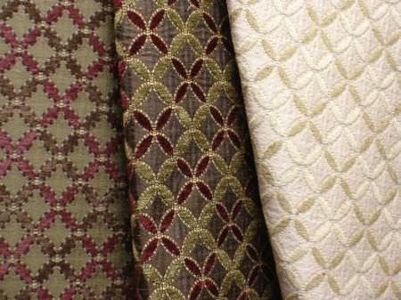 Jim Dickens -  Isabella Fabric Collection - A pattern of small pointed ovals in cream and dark shades of green and purple ongreen, dark brown and ivory coloured fabric backgrounds