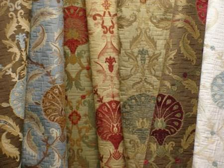 Jim Dickens -  Olympos Fabric Collection - Brown, blue, green, red, gold, dark purple, white and cream patterns on seven swatches of co-ordinating fabrics
