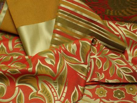Jim Dickens -  Perla Fabric Collection - Patterned and striped fabrics in bright red, pumpkin orange, brown-green and a metallic shade which is a mix of gold and green