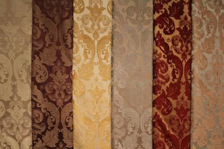 Jim Dickens -  Trafalgar Fabric Collection - Very ornately patterned fabrics in six different colour combinations including red and brown, silver and brown, and cream and gold