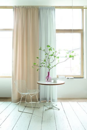 Jones Interiors -  Boca Fabric Collection - A round white table with a white mesh chair, plain white and cream curtains, a white bowl, a clear pink vase and a branch
