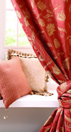 Jones Interiors -  Bronte Fabric Collection - Gold florals on terracotta curtains tied back with matching fabric, with patterned orange and plain cream fringed cushions