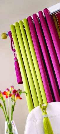 Jones Interiors -  Cavendish Fabric Collection - A plain lime green curtain and a plain berry coloured curtain, with matching tassel tiebacks, a clear vase and a white chair