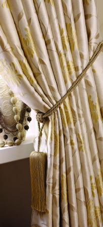 Jones Interiors -  Chrysanthemum Fabric Collection - A gold tassel tieback around elegant cream and yellow-gold floral curtains, beside cream-green and dark brown pompom trims
