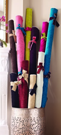 Jones Interiors -  Forte Fabric Collection - Ten rolls of plain fabric in various bright and dark colours, each tied with a different ribbon in a large pewter bucket