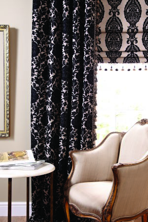 Jones Interiors -  Intermezzo Fabric Collection - Curtains and a blind with two different onate black and cream patterns, a gold framed cream armchair, and a round table