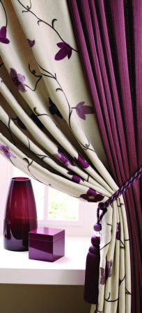 Jones Interiors -  Jasmine Fabric Collection - A plain mulberry curtain, a cream curtain with mulberry leaves, a mulberry cord tieback, a red box and a burgundy vase