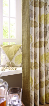 Jones Interiors -  Kew Fabric Collection - Pale green, grey and cream leaf print curtains and cushions, near some beaded trim, with a glass and a clear decanter