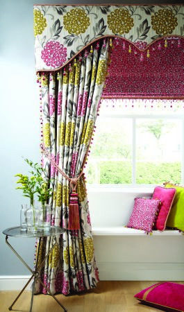 Jones Interiors -  Opulence Fabric Collection - Curtains and pelmet with a large pink, green, grey and cream floral design, pink tiebacks, pink and green cushions and a table