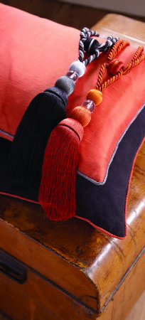 Jones Interiors -  Parade Fabric Collection - A wooden chest topped with a plain black cushion, an orange cushion, and plain black and orange tassel tiebacks