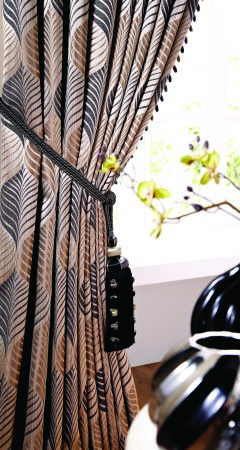 Jones Interiors -  Rufford Fabric Collection - Grey, white and beige patterned cushions with a black tassel tieback, and small silver and black coloured vases