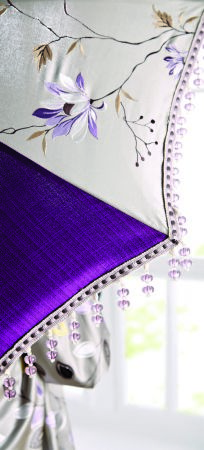 Jones Interiors -  Serenity Fabric Collection - A lampshade made from plain purple fabric, white fabric with a purple and green floral pattern, and lilac beaded trim