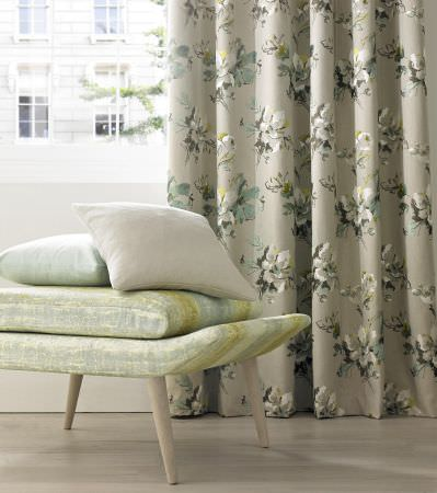 Kai -  Akina Fabric Collection - Beige curtain decorated with a very elegant floral design and plain white and light green cushions on a vibrant chair