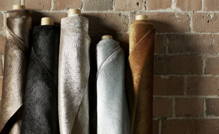 Kai -  Allegra Fabric Collection - Five rolls of fabric against a brick wall, each plain with a soft fluffy texture, in brown, black, silver, grey and copper